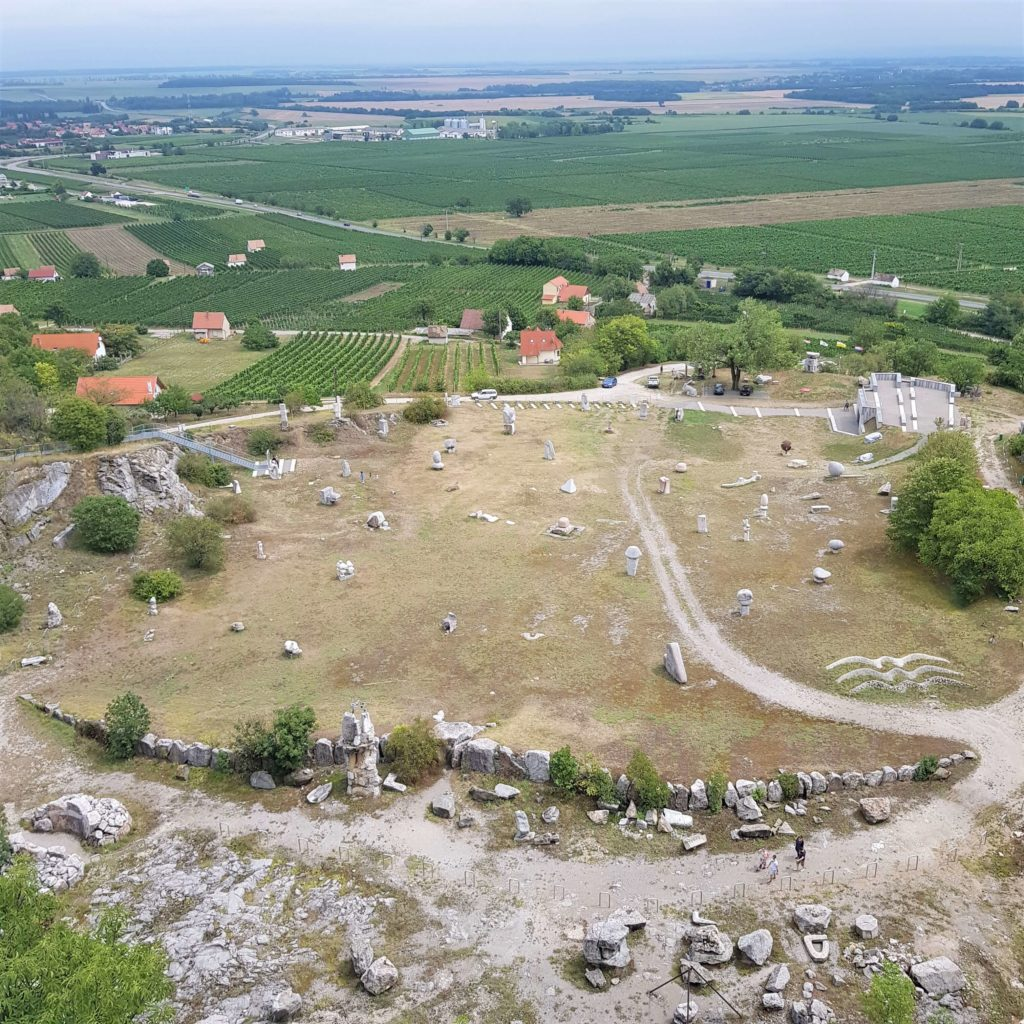 View from top of the quarry featuring stone statues and wineyards