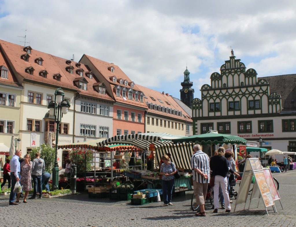Weimar: locals shopping from the market stalls. In the background, the tourist information office