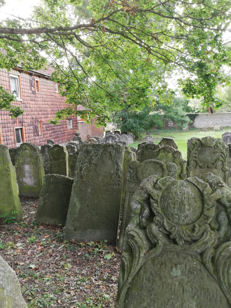 The image depicts the condition of the Jewish cemetery